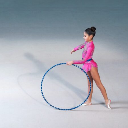 Gymnast In A Pink Suit Doing Hoop Exercise